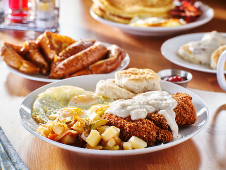 chicken fried steak covered in gravy with sunny side up eggs and breakfast foods Reklamní fotografie