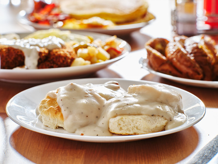 biscuits and gravy with breakfast foods on plate Standard-Bild