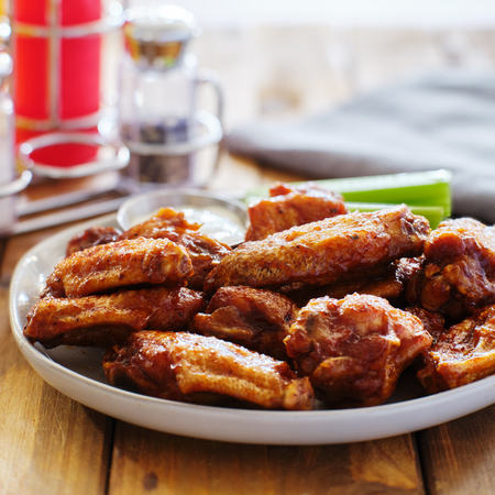 plate of bbq chicken wings with ranch dip and celery sticks on wooden table