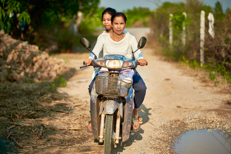 Thai mother and daughter riding motorbike together in rural thailand on road Reklamní fotografie