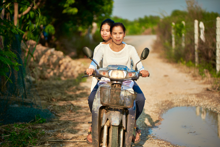 Thai mother and daughter riding motorbike through rural thai road