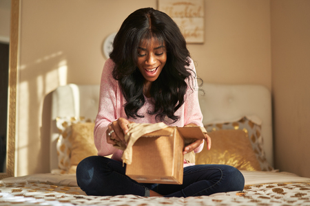 Happy african american woman unboxing package in bedroom Stockfoto
