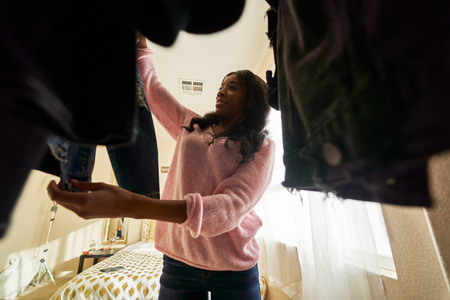 African american woman looking through closet at clothes