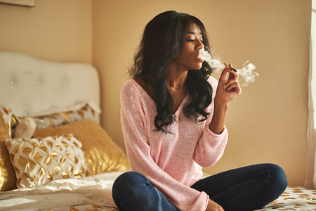 African american woman smoking marijuana joint while sitting on bed at home Stok Fotoğraf - 120470244