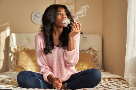 Afroamerikanische Frau raucht Marihuana Joint, während sie zu Hause auf dem Bett sitzt on