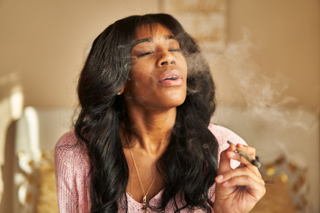 African american woman smoking marijuana joint while sitting on bed at home