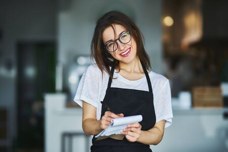 young waitress ready to take order on notepad in restauran Banque d'images