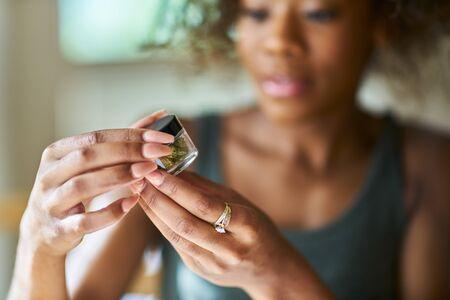 一名非裔美国妇女在近距离观察一瓶大麻