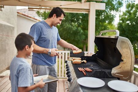 father and son grilling hot dogs together on backyard gas grill Standard-Bild