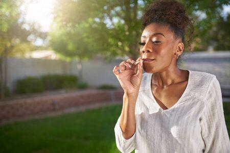 抽烟大麻关节的愉快的非洲裔美国人妇女在后院