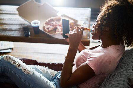 Frau bleibt lange auf, entspannt sich zu Hause vor dem Fernseher und isst Pizza?