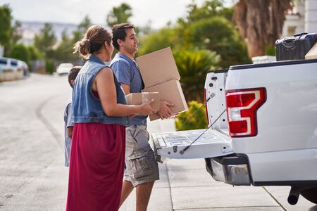 hispanic family moving boxes out of pickup truck into house Stock Photo