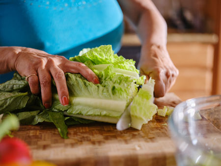 older woman cutting up romaine lettuce