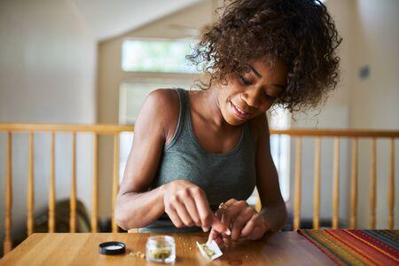 非裔美国妇女在家里滚动大麻大麻从药房买的大麻