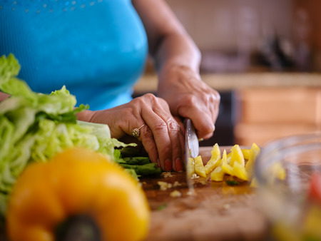 older thai woman cutting up yellow bell pepper on board to make salad