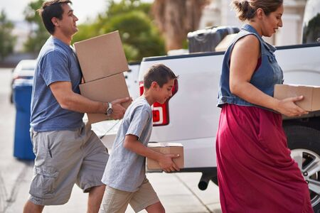 hispanic family moving boxes out of pickup truck into house