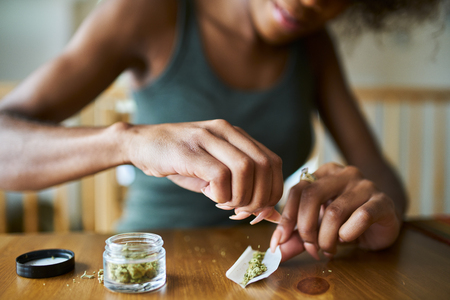 african american woman at home rolling marijuana joint close up Reklamní fotografie