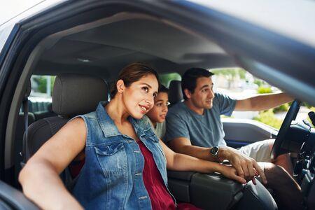 Familia hispana con madre, padre e hijo sentados en un camión mirando afuera Foto de archivo