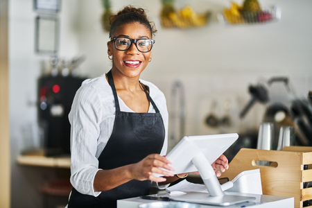 Friendly shop assistant ready to take customer orders at register in restaurant