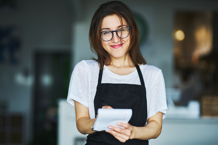 Young waitress ready to take order on notepad in restaurant