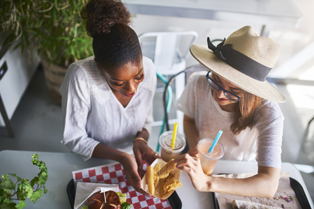 Two woman sharing healthy vegan yucca root fries and eating meal together at vegan restaurant