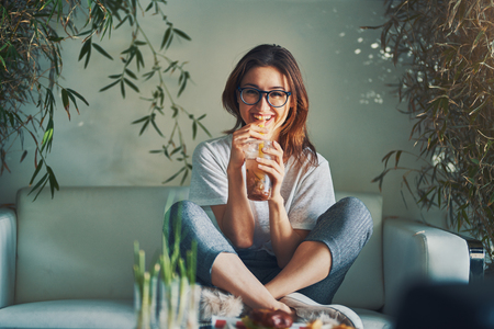 Smiling woman drinking healthy fruit infused beverage while relaxing on sofa in trendy restaurant