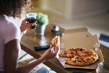 woman eating pizza and drinking cola while sitting on sofa watching tv in home late at night Reklamní fotografie