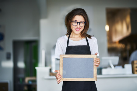 Friendly smiling shop assistant holding blank chalkboard sign in restaurant