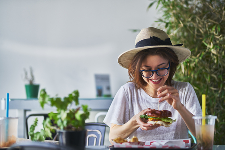 Happy smiling woman eating healthy vegan burger at trendy restaurant