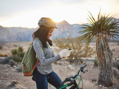 fit african american on bike taking a rest to use smartphone Stock Photo