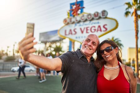 mature tourist couple taking selfies in front of iconic welcome to las vegas sign