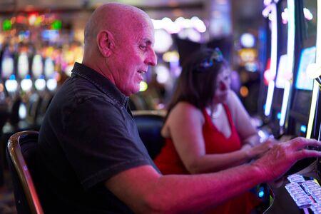 elderly tourist playing slot machines and gambling in casino