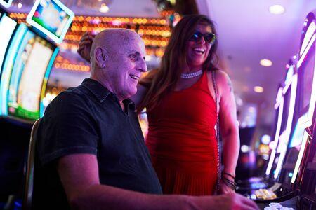 elderly couple gambling on slot machine in casino