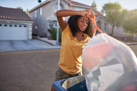 african american woman taking out the trash in las vegas neighborhood, 版權商用圖片
