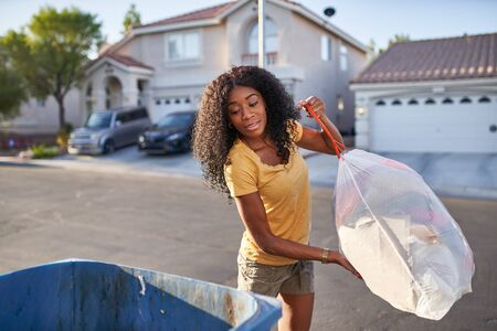 african american woman taking out the trash in las vegas neighborhood, 版權商用圖片