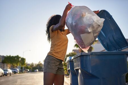 African american woman taking out the trash in las vegas neighborhood,