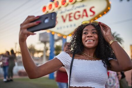 African american woman taking selfie with smartphone in front of welcome to las vegas sign Standard-Bild