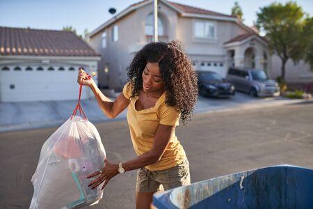 African american woman taking out the trash in las vegas neighborhood,
