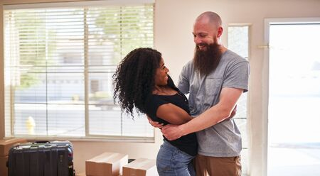 Happy interracial couple embracing after moving into new house