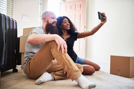 Interracial couple taking selfie together while moving into new home