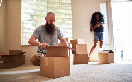 interracial couple moving into new house with boyfriend opening box