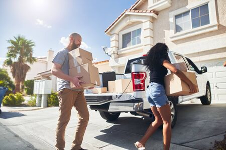 interracial couple moving into new home and taking boxes out of truck Standard-Bild