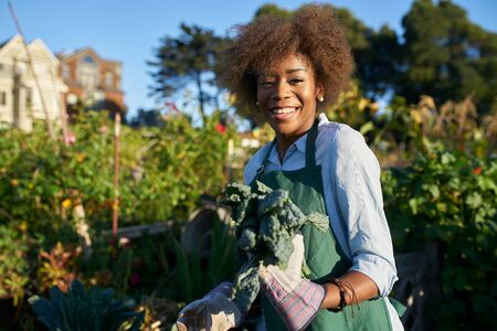 Proud diverse millennial posing with freshly picked kale at urban community communal garden