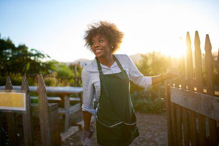 African american female gardener walking out of community urban garden at end of day Standard-Bild