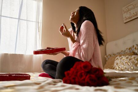 Happy african american woman eating romantic valentines chocolates from heart shaped box while sitting on bed at home Standard-Bild
