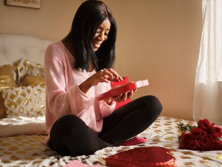 Young african american woman eating valentines day chocolates from romantic heart shaped box