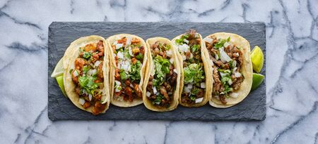 row of mexican street tacos on slate with carne asada and al pastor in corn tortilla Standard-Bild