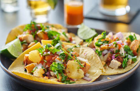 Colorful grilled pineapple and chicken street tacos on plate with lime