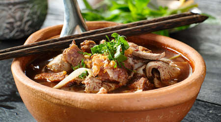 Thai bowl of beef noodle soup in clay pot with duck liver