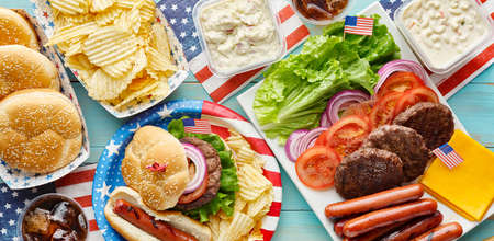 4th of july feast with burgers and hot dogs on picnic table Imagens